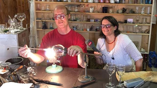 Ein Mann bearbeitet über einer Flamme Glas, daneben sitzt eine Frau mit SRF-Mikrofon. Beide tragen eine Schutzbrille.