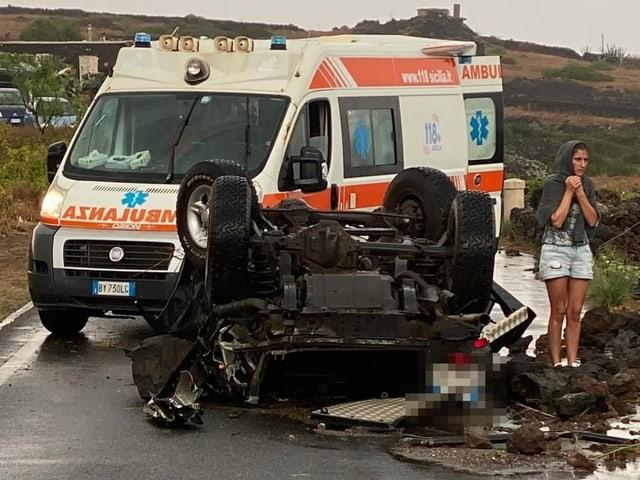 Eine Frau und ein zerstörter Wagen stehen vor einem Krankenwagen