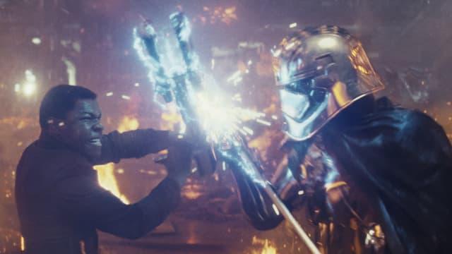 Filmszene: Zwei Figuren kämpfen mit leuchtendnen Waffen.