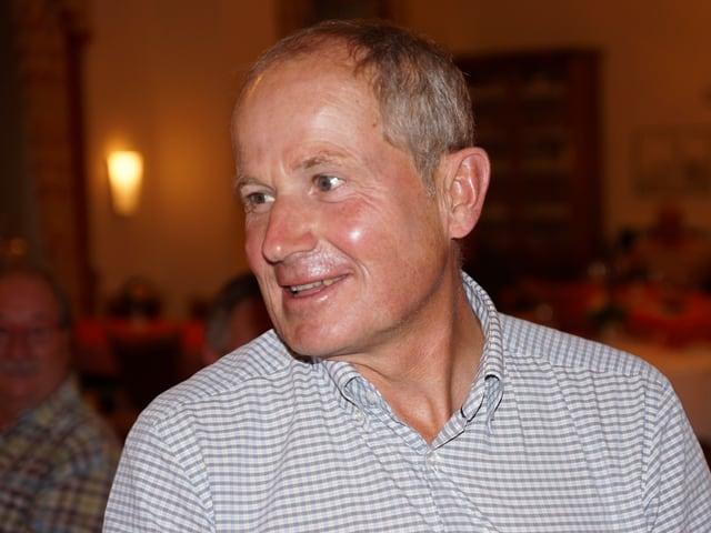 Der Mann mit kariertem Hemd blickt belustigt nach links.