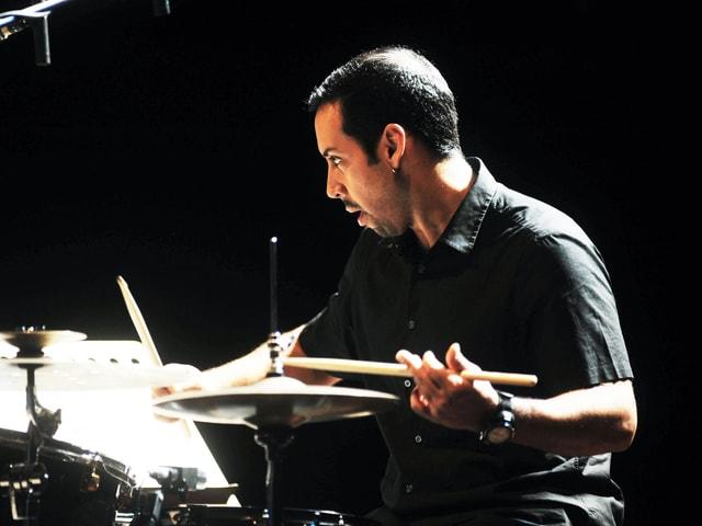 Ein Mann mit kurzen dunklen Haaren sitzt an einem Schlagzeug und spielt konzentriert.