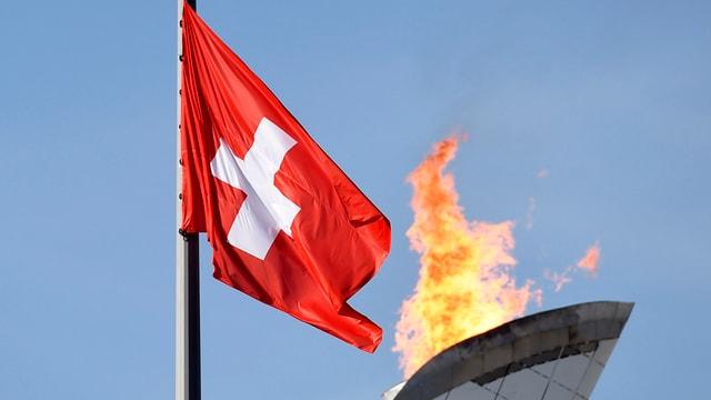 Purtret d'ina bandiera svizzra davant il fieu olimpic.