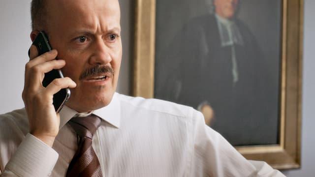 Ein glatzköpfiger Mann im Hemd telefoniert.