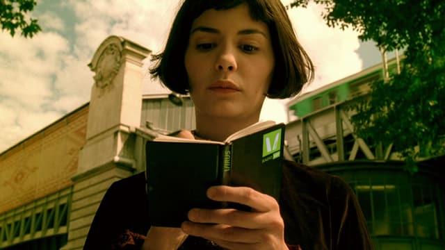 Audrey Tautou liest in einem Buch im Film Die fabelhafte Welt der Amélie