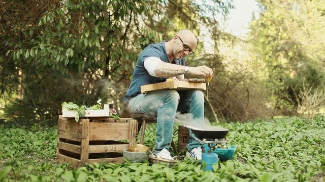 René Schudel sitzt in der Natur und kocht auf einem Gasherd.