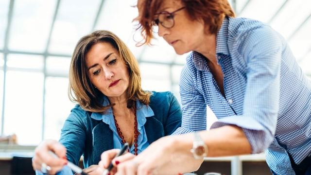 Zwei Frauen mittleren Alters arbeiten gemeinsam an einem Pult.