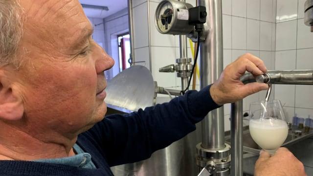 Christian Herzog füllt ein Glas unfiltrierten Wein in ein Glas ab.