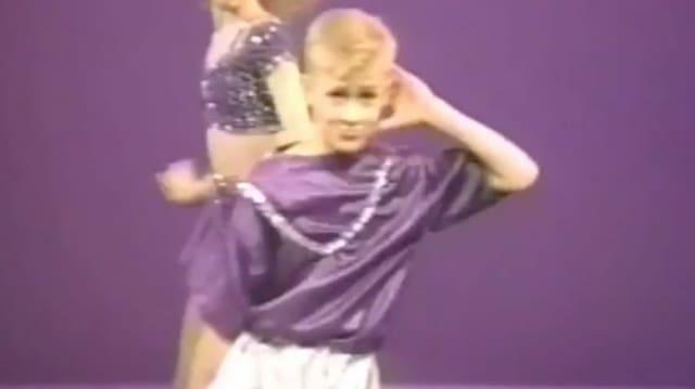 Ein Junge in violettem T-Shirt und silbrigen Hosen lächelt in die Kamera. Ein Arm hält er hinter den Kopf.