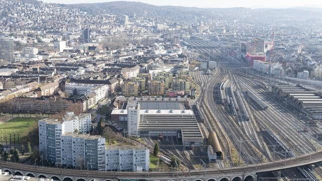 Ein Blick von oben auf die Stadt Zürich. Inder Bildmitte Zuggleise, links daneben eine neue Siedlung.