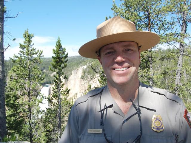 Ein Portät von Tim Townsend. Er trägt einen Hut und steht vor der Kulisse des Nationalparks.