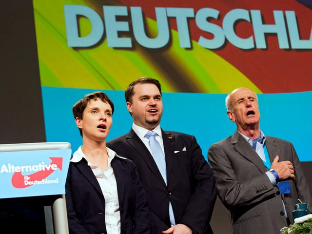 """Zwei Politikerinnen und zwei Politiker nebeneinander stehend, singend, hinter ihnen ist eine deutsche Flagge projiziert, darauf steht gross """"Deutschland""""."""