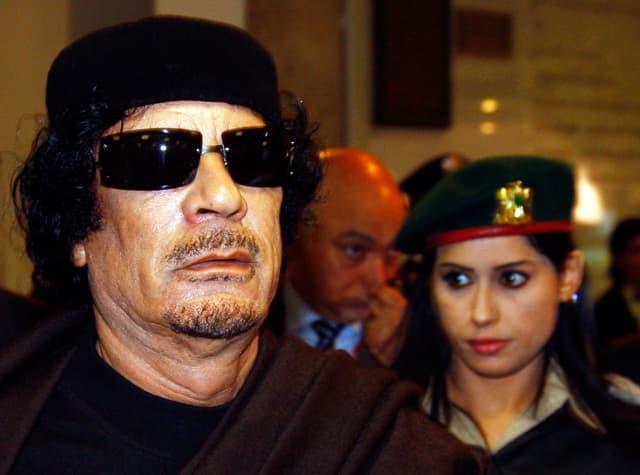 Nahaufnahme Gaddafis mit Sonnenbrille. Neben ihm steht eine seiner weiblichen Bodyguards.