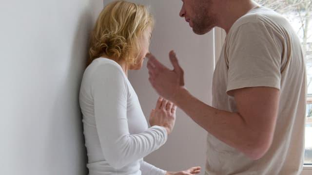 Eine Frau steht in der Ecke, wird bedrängt von einem Mann.