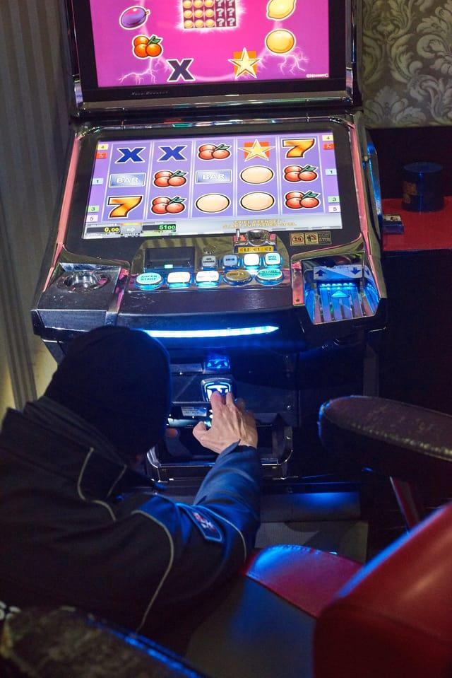 Polizist kniet vor buntem Spielautomat.
