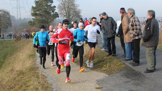 Mehrer Läufer rennen auf einem Weg.