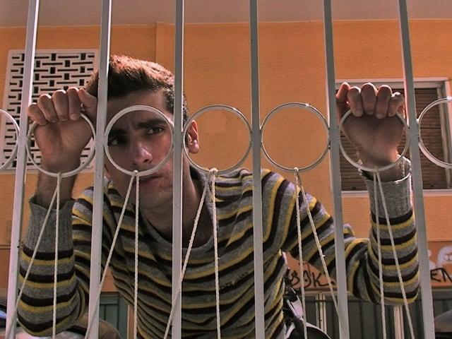 Szene aus dem Film mit einem Mann hinter einem Gitterzaun.