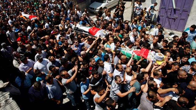 Palästinenser tragen drei mit Flaggen bedeckte Särge