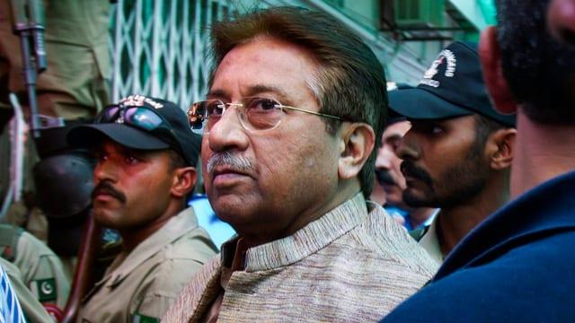 Musharraf in Mitten von Polizeikräften.