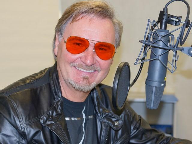 Mann mit orangefarbener Brille im Radiostudio.