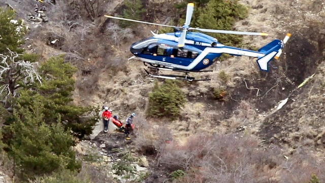 In helicopter e persunas da salvament al lieu d'accident.