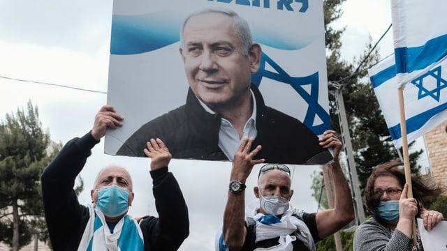 Protestierende, die ein Plakat von Netanjahu in den Händen halten.