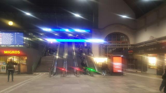 Leere Halle im Bahnhof Basel, Menschen auf der Rolltreppe.