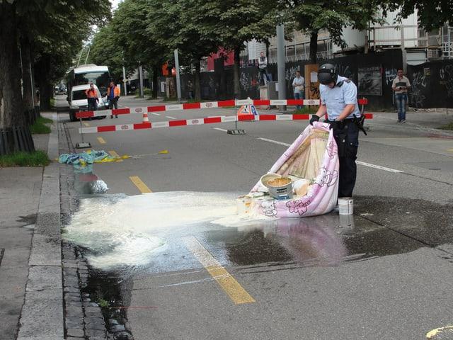 Ein Polizist bei Aufräumarbeiten an der blockierten Hohlstrasse