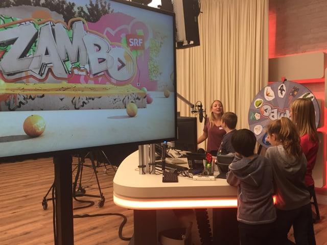 Eine Gruppe von Kindern steht um das Radiopult an dem Anna etwas erklärt.
