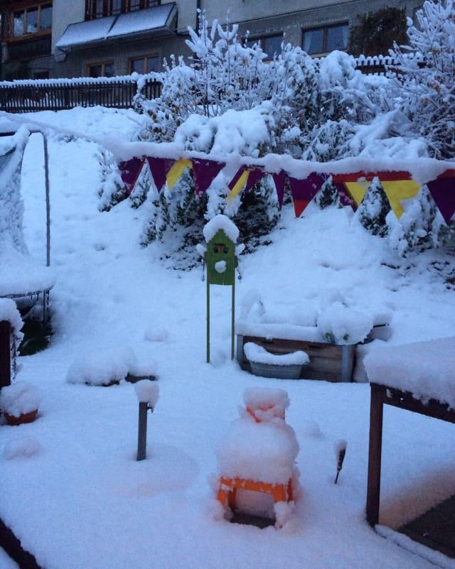 Im Garten liegt eine geschlossene Schneedecke. Die Kinderspielsachen müssen wohl ausgegraben werden.