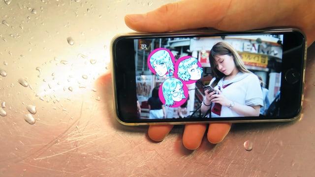 Eine Hand hält ein Smartphone. Darauf ist eine Frau zu sehen, die ein Smartphone hält. Daneben gezeichnete Manga-Köpfe.