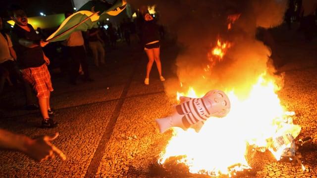 Demonstranten werfen eine aufblasbare Puppe, die einen Sträfling darstellt, in ein Feuer.
