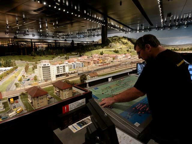 Mann an Stellwerkpult steuert die Modelleisenbahnanlage im Museum Kaeserberg
