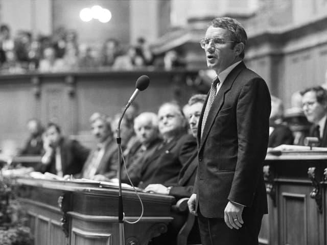 Arnold Koller steht vor Mikrofon im Parlament