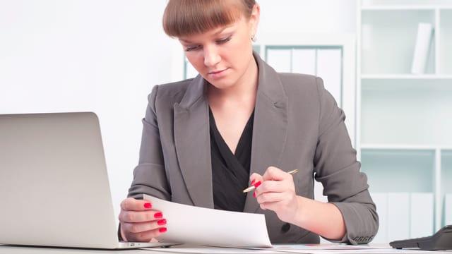 Frau studiert Akten bei Computer