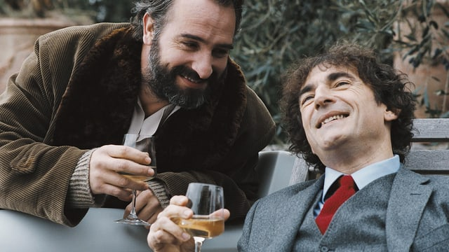 Zwei Männer trinken in einem Garten Weisswein.