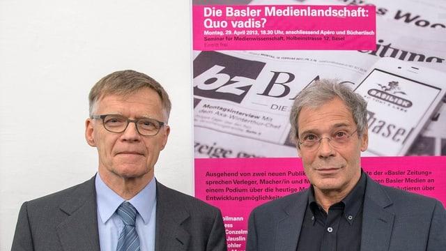 Peter Wanner mit Krawatte und Rolf Bollmann im schwarzen Hemd vor Podiumsplakat