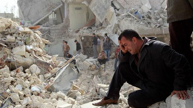 Weinender Mann in Trümmern