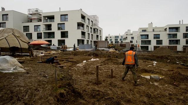 Neue Blöcke werden gebaut; es sind auch Bauarbeiter zu sehen.