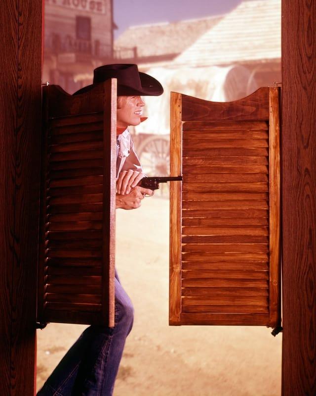 Ein Mann mit Pistole öffnet die Tür eines Salons.