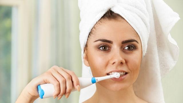 Eine Frau im Bad putzt sich die Zähne.