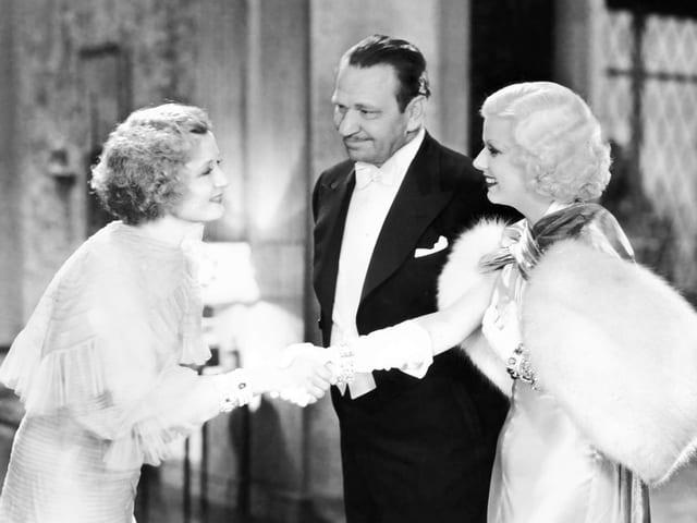 Zwei elegant gekleidete Frauen schütteln sich die Hände, ein Mann steht dazwischen und lächelt.