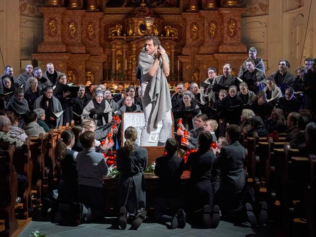 In einer Kirche - ein Mann in der Mitte steht in einem Sarg - rundherum Menschen.