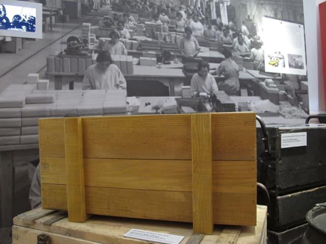 Holzkisten und Bild einer Fabrikhalle im Hintergrund