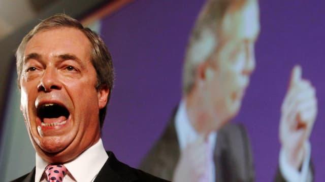 Nigel Farage spricht, sein Mund steht offen, er schwitzt, im Hintergrund eine Projektion von sich selber.