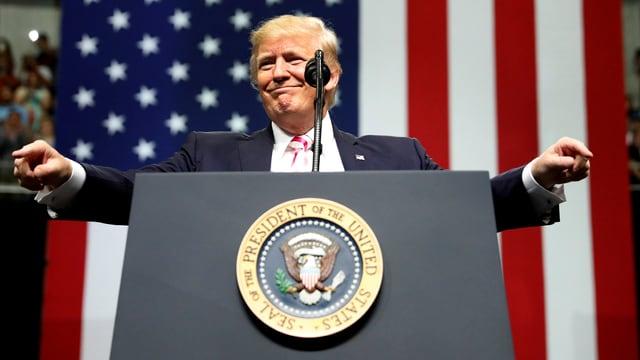 Donald Trump an einem Rednerpult mit selbstgefälliger Miene.