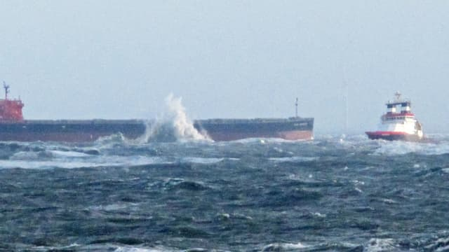 Der auf Grund gelaufene Frachter, an dem die Wellen hochgehen und der Schlepper.