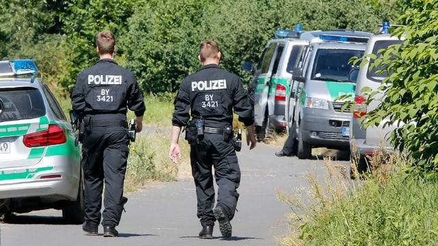 Zwei Polizisten und Polizeifahrzeuge
