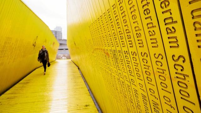 Die «Luchtsingel», eine gelbe Brücke. Eine Fussgängerin geht über die Brücke.