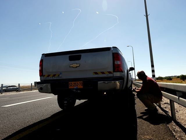 Ein Mann nimm hinter einem Auto Deckung bei einem Raketenangriff in Israel.