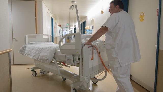 Pflegefachmann im Spital schiebt ein leeres Bett durch einen Gang